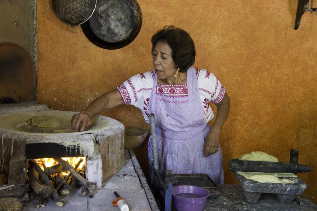 Doña Cata Cuautle echando tortillas, el tlecuilli sobre una base. Fotógrafo José Loreto Morales.