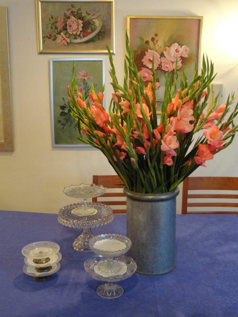 Gladiolas –estas eran las flores favoritas de mi papá- en bote nevero de lamina; mantel de damasco comprado en Zara Home; pasteleros antiguos diversos tamaños comprados la Plazuela de los Sapos y oleos con el tema de rosas, -de primera mitad de siglo XX-. 2015, Fotógrafa Lilia Martínez.
