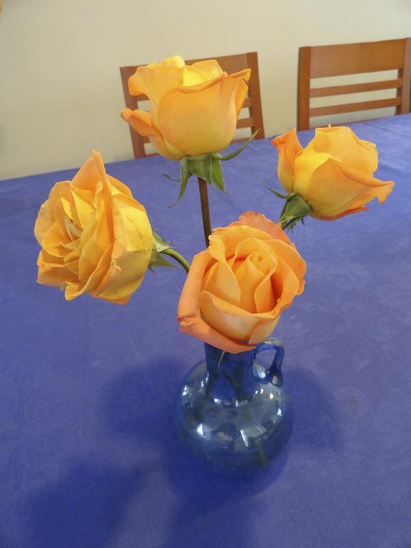 Rosas anaranjadas, en jarrita de vidrio soplado, en color azul tornasolado, adquirida en un bazar y mantel de damasco comprado en Zara Home. Fotógrafa Lilia Martínez.