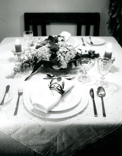 """El mantel y la carpeta con tira bordada los hice especialmente para esta mesa, las servilletas son de lino y los servilleteros son unas coronitas de Virgen, la vajilla es la que llamo """"Lolis"""", las copas son """"Principe de Gales"""", las flores son de una querida amiga Edith Besenfelder (florista alemana que por algunos años estuvo en Puebla) y los candeleros son regalo mi hermana Pily. 2000, Fotógrafa Lilia Martínez. Colección Familia RojanoMartínez."""