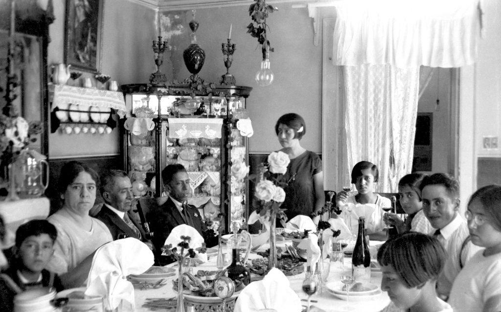 Dr. Liborio Ramírez y su familia en el aperitivo, gala poblana en la mesa del comedor para la comida de diario. Fotógrafo Alfonso Ramírez, Fototeca Lorenzo Becerril A.C.