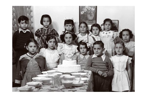 """Fiesta infantil, mesa con pastel de dos pisos y vajilla """"Lolis"""". Fotografía publicada en libro """"Casa poblana. El escenario de la memoria personal"""". Fototeca Lorenzo Becerril A.C."""